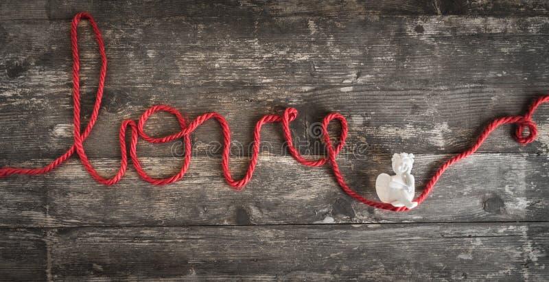 O amor da palavra escrito com uma linha de lã vermelha onde um anjo esteja foto de stock