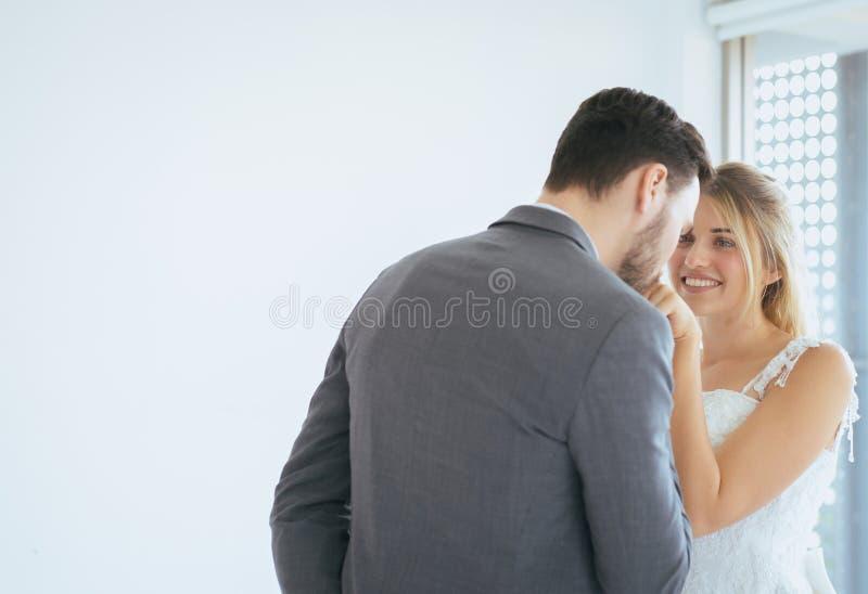 O amor e o par rom?ntico est?o beijando com dan?a junto no fundo branco, apreciando no dia do casamento foto de stock royalty free
