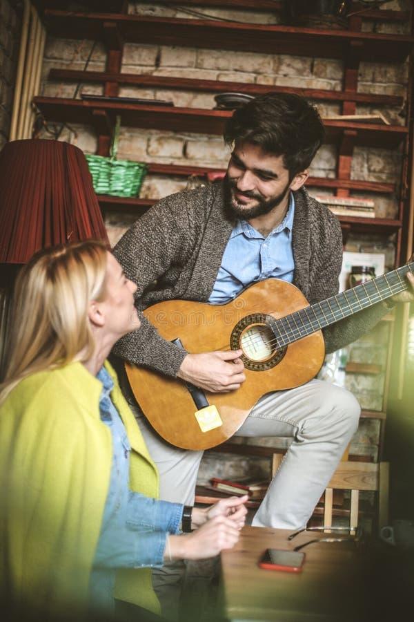 O amor expresso que joga a guitarra acústica sua menina é sempre romanti foto de stock royalty free