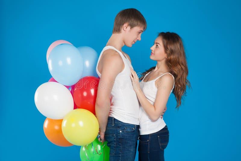 O amor novo de sorriso acopla guardarar balões no estúdio fotografia de stock royalty free