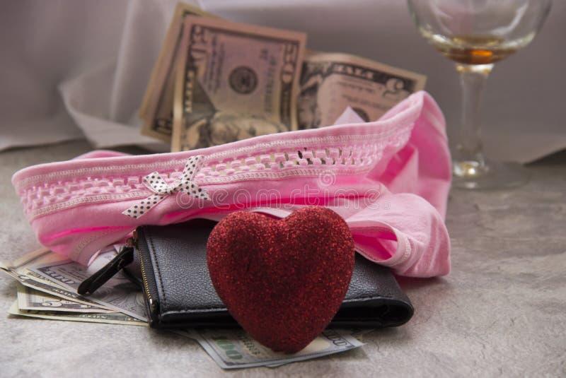 O amor para o dinheiro ? prostitui??o Uma folha amarrotada, um vidro do vinho e o dinheiro em seu roupa interior s?o taxas do sex fotos de stock