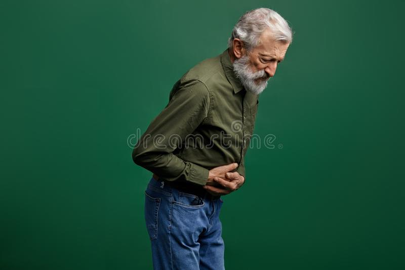 O ancião com a barba longa cinzenta tem problemas com estômago fotos de stock royalty free