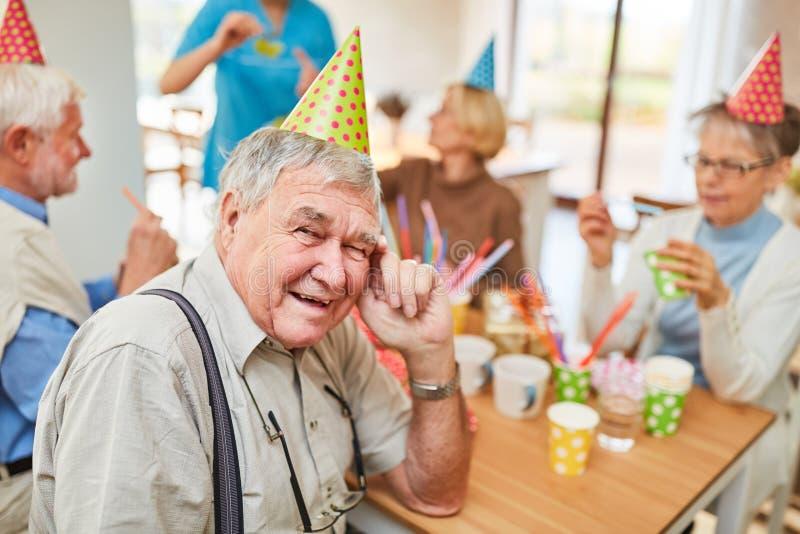 O ancião com chapéu do partido está comemorando o aniversário imagem de stock royalty free