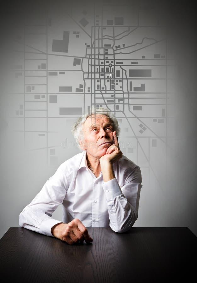 O ancião está procurando uma rota no mapa da cidade imagem de stock royalty free