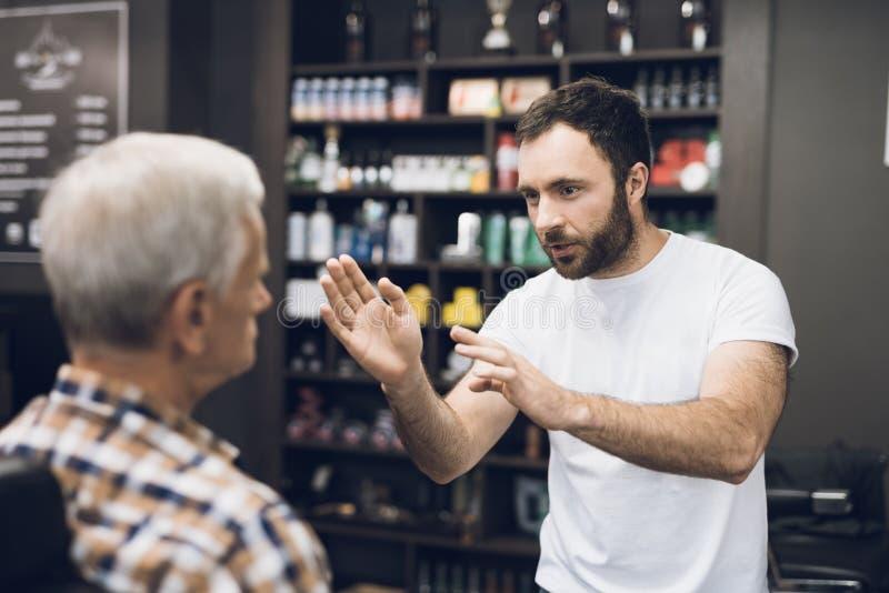 O ancião está sentando-se na cadeira do ` s do barbeiro em um barbeiro do ` s do homem, aonde venha cortar seu cabelo fotos de stock