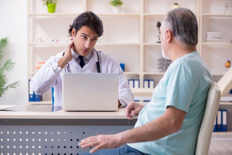 O anci?o que visita o doutor masculino novo imagens de stock royalty free