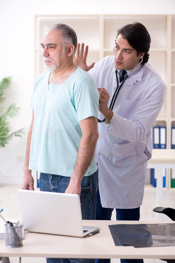 O anci?o que visita o doutor masculino novo fotografia de stock