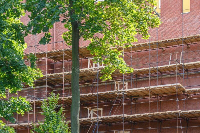 O andaime, com assoalhos de madeira, é instalado perto de uma parede de tijolo alta imagens de stock