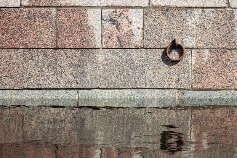 O anel da amarração montou na parede do molhe da pedra do granito foto de stock