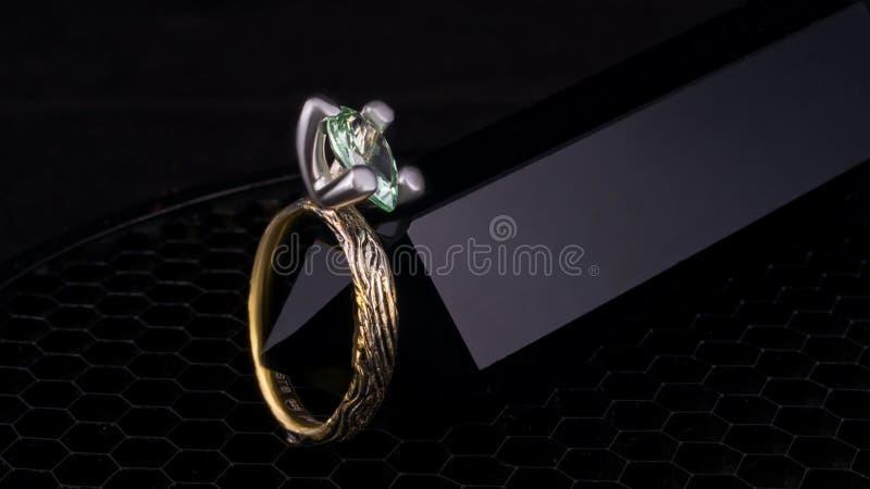 O anel de ouro está estando no fundo preto com a pedra esmeralda da turmalina da malaquite grande fotos de stock royalty free