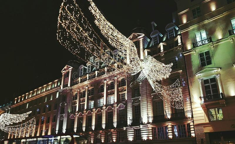 O anjo de néon iluminou a construção pública do europa de Inglaterra da luz da cidade do xmas dezembro Londres Grâ Bretanha da de imagens de stock royalty free