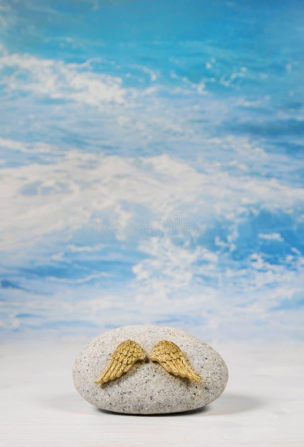 O anjo dourado voa com a pedra no fundo azul do céu para o spir imagem de stock royalty free