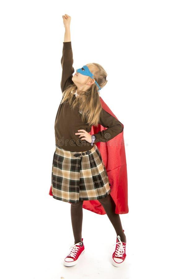 7 o 8 anni del giovane bambino femminile in costume dell'eroe eccellente sopra l'esecuzione dell'uniforme scolastico felice ed em fotografia stock