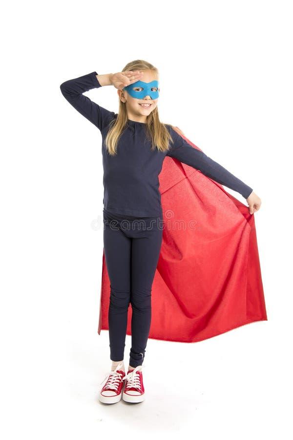 7 o 8 anni del giovane bambino femminile della scolara nell'esecuzione del costume dell'eroe eccellente felice ed emozionante iso immagini stock