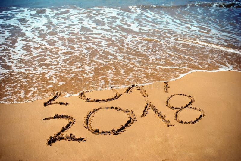 O ano novo 2018 é conceito de vinda - a inscrição 2017 e 2018 em uma areia da praia, a onda está cobrindo os dígitos 2017 Celebri imagens de stock royalty free