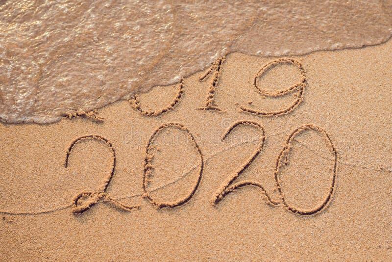 O ano novo 2020 é conceito de vinda - a inscrição 2019 e 2020 uma areia da praia, a onda está cobrindo quase os dígitos 2019 foto de stock