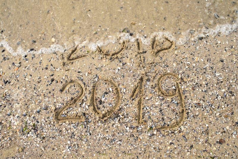 O ano novo 2019 substitui 2018 no conceito da praia do mar, copia o espaço Onda que começa cobrir os dígitos 2018 O ano novo 2019 imagem de stock royalty free