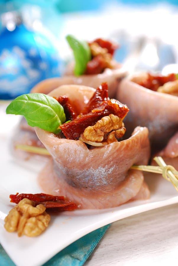 O aperitivo dos arenques rola com tomate e as nozes secados para o chr imagens de stock royalty free