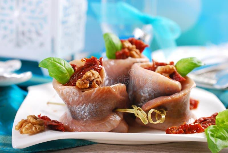 O aperitivo dos arenques rola com tomate e as nozes secados para o chr fotos de stock royalty free