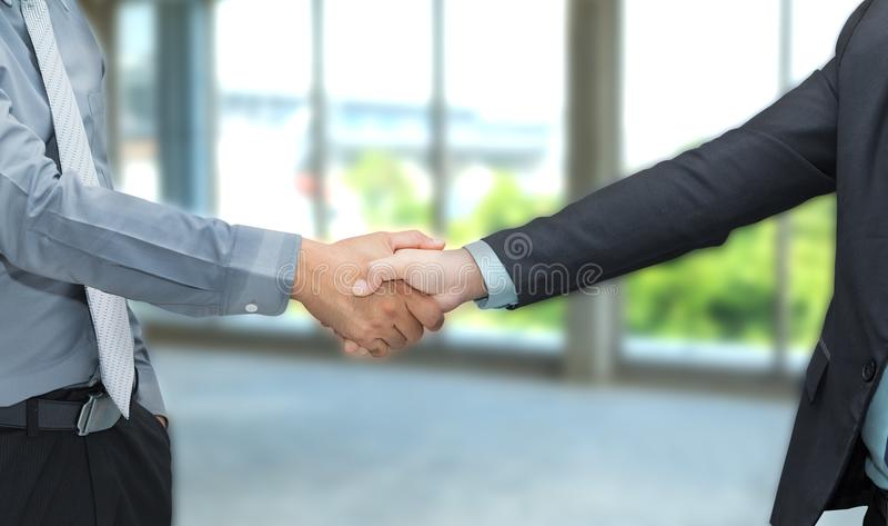 O aperto de mão da parceria de dois homens de negócios concorda o negócio junto dentro fotos de stock