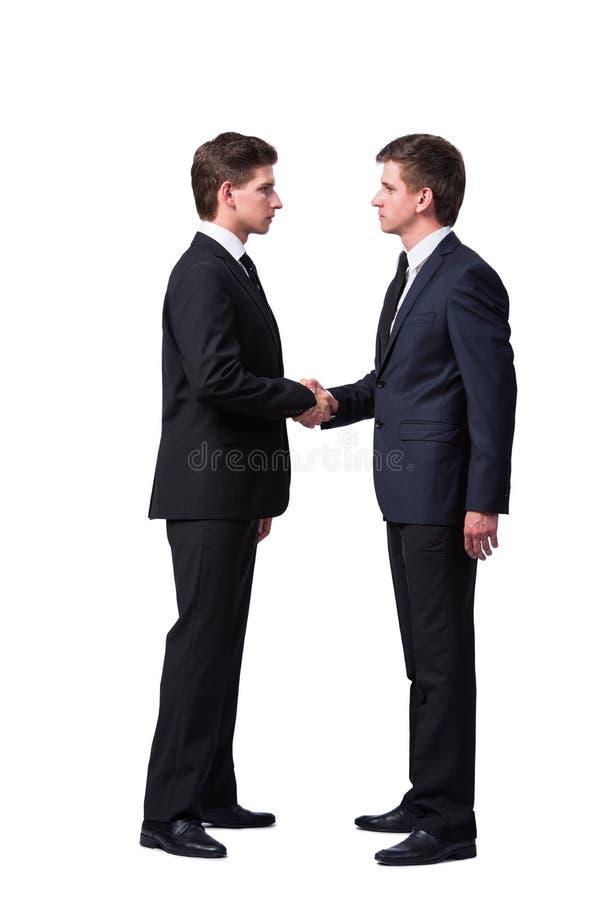 O aperto de mão de dois irmãos gêmeos isolado no branco fotografia de stock royalty free