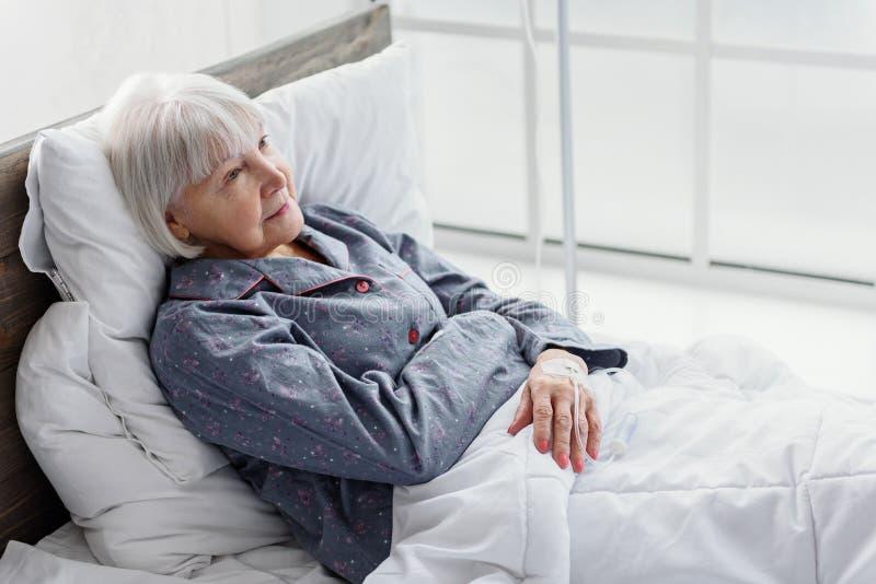 O aposentado contente está na garrafa do gotejamento que reclina na cama imagem de stock