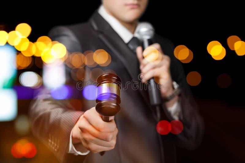O apresentador com um microfone em sua mão guarda um leilão fotografia de stock royalty free