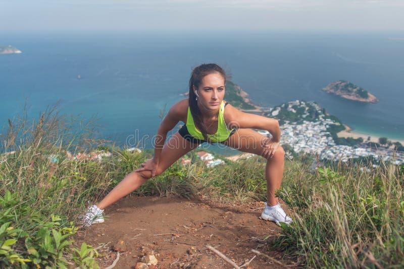 O aquecimento novo do atleta fêmea antes de dar certo esticando seus pés que fazem o lado investe contra o exercício que está no imagem de stock