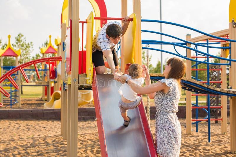 O ar livre feliz do rapaz pequeno no campo de jogos com seus pais fotos de stock royalty free