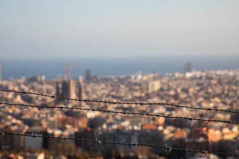 O arame farpado focalizado com a cidade de Barcelona borrou no fundo imagens de stock royalty free