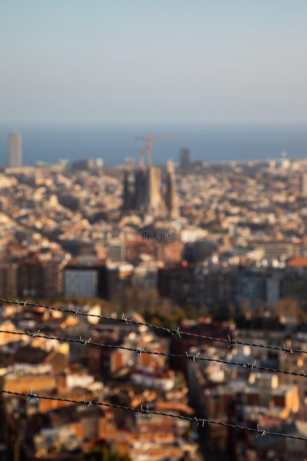 O arame farpado focalizado com a cidade de Barcelona borrou no fundo imagem de stock