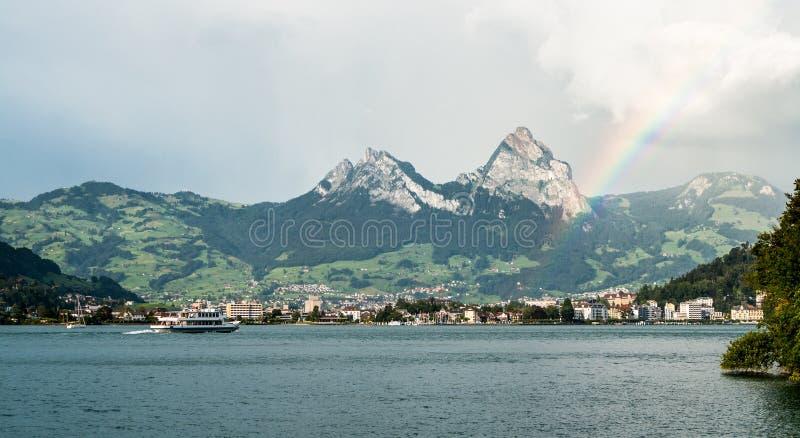 O arco-íris brilha após uma chuva no lago lucerne imagens de stock