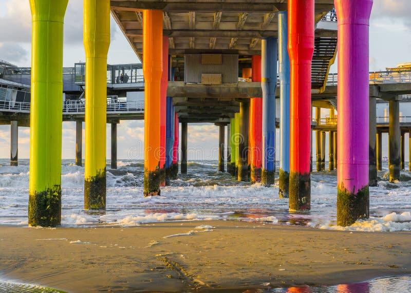 O arco-íris coloriu os polos de pedra sob o cais da praia de scheveningen o holandês com areia e ondas no no mar imagens de stock royalty free
