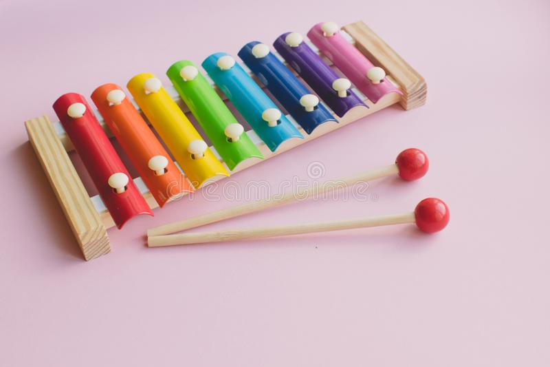 O arco-íris coloriu Toy Xylophone de madeira no bacground cor-de-rosa glockenspiel do brinquedo feito do metal e da madeira fotografia de stock royalty free