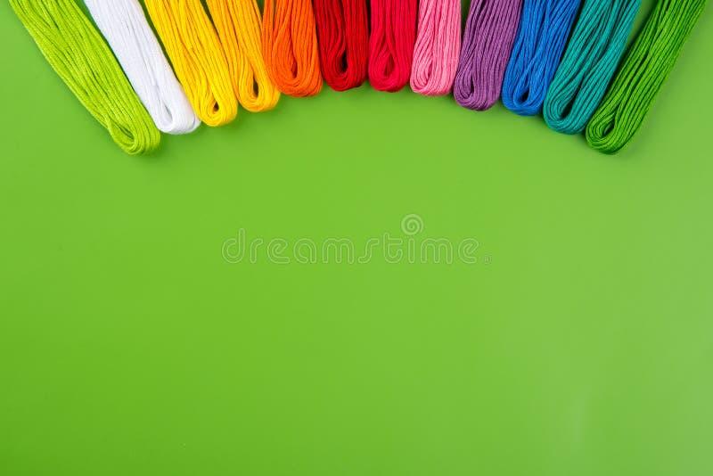 O arco-íris do bordado colore o Floss em um fundo verde Conceito para costurar e bordado Vista superior imagem de stock royalty free