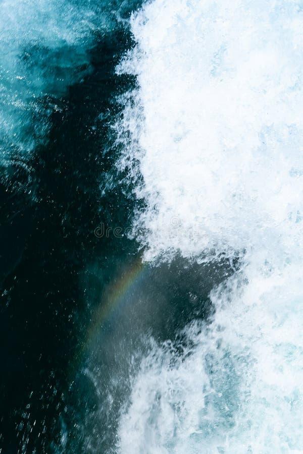 O arco-íris pequeno para aparecer atrás do barco na água raging azul fotografia de stock