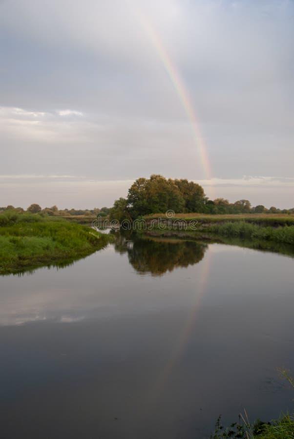 O arco-íris romântico é dado por um rio quieto no fundo de um céu claro da manhã imagens de stock