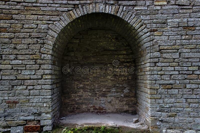 O arco de pedra da antiguidade do tijolo é uma janela Europa do Norte, o castelo Parede da fortaleza feita de tijolos cinzentos foto de stock royalty free