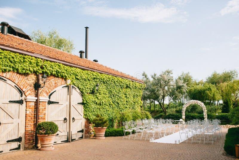 O arco do casamento é decorado com as flores por rosas ao lado da construção antiga do celeiro Com cadeiras do vintage em uma lag imagens de stock