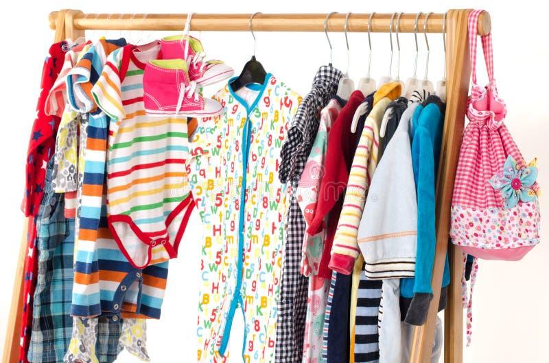 O armário do molho com roupa das crianças arranjou em ganchos imagens de stock royalty free