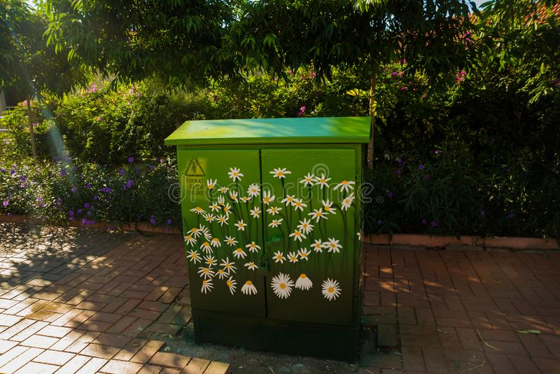 O armário do transformador é pintado com cores: margaridas em um fundo verde Um sinal de alta tensão do perigo em uma caixa elétr fotografia de stock