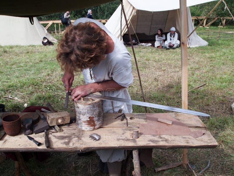 O armeiro do ferreiro faz uma espada imagens de stock royalty free