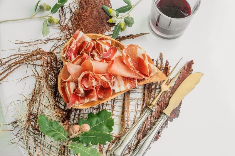 O aroma do presunto e das especiarias, cortado finamente em uma tabela branca com a cutelaria e vinho tinto antigos do pão foto de stock royalty free