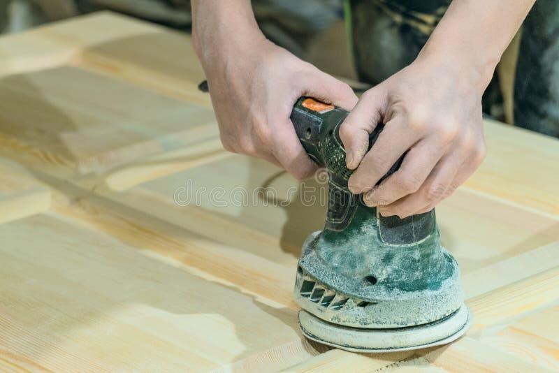 O arpenter do ¡ de Ð lustra a superfície de madeira da folha da porta Máquina de moedura orbital excêntrica elétrica imagens de stock