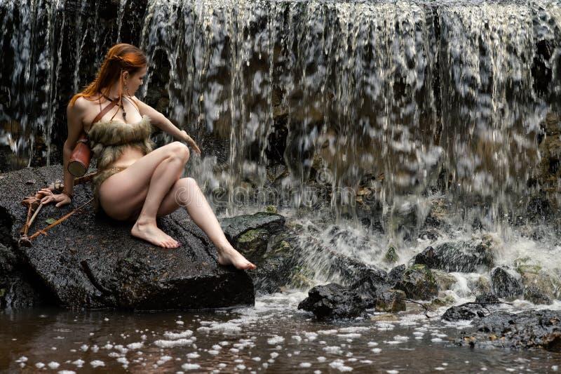 O arqueiro fêmea novo aprecia a cachoeira foto de stock