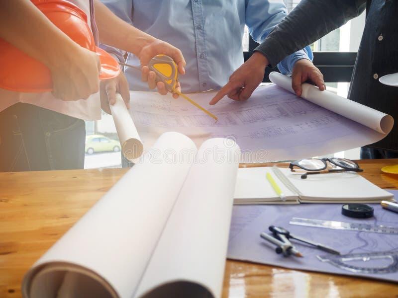 O arquiteto, o coordenador e o contramestre discutem com o modelo fotos de stock