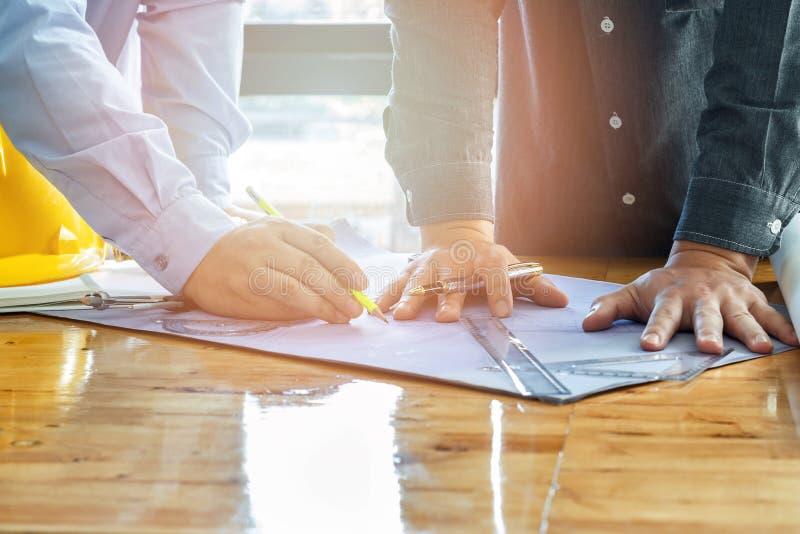 O arquiteto, o coordenador e o contramestre discutem com o modelo fotos de stock royalty free