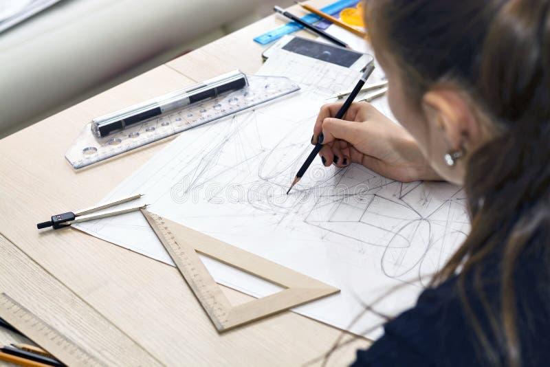 O arquiteto da menina tira um plano, projeto, formas geométricas pelo lápis na grande folha de papel na mesa de escritório foto de stock