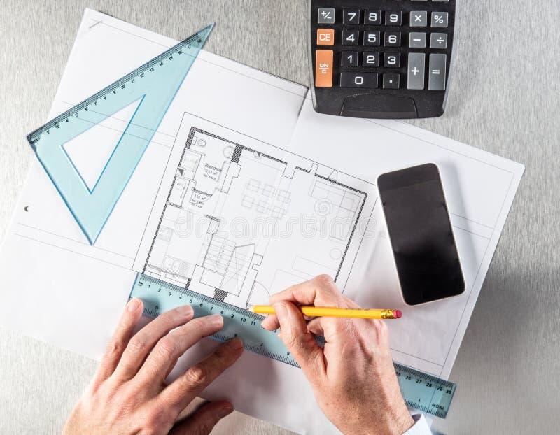 O arquiteto entrega a fatura das medidas, trabalhando na mesa para o conceito da construção foto de stock