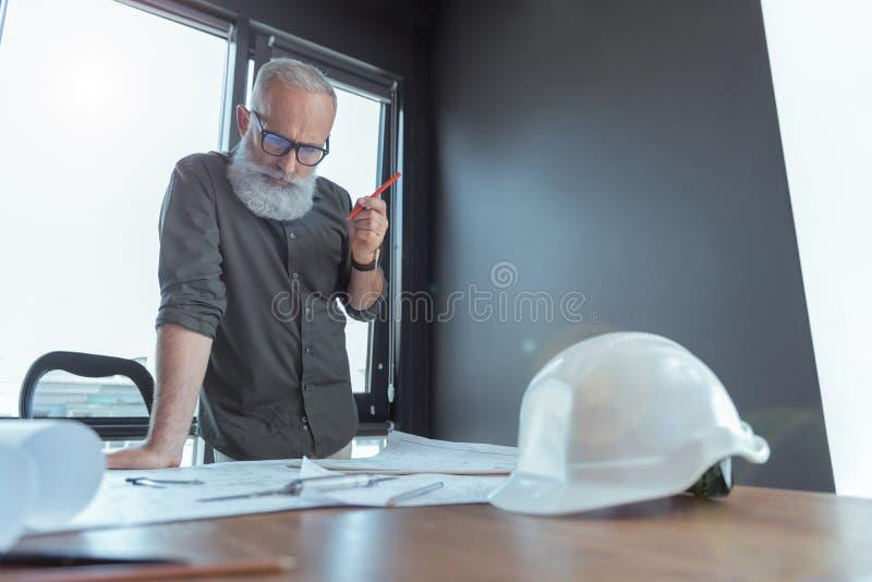 O arquiteto idoso seguro está trabalhando no projeto imagens de stock